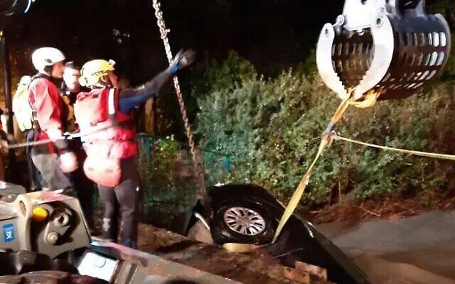 Des secouristes extraient une voiture des eaux, à Binyamina. (Crédit : Fire and Rescue Service)