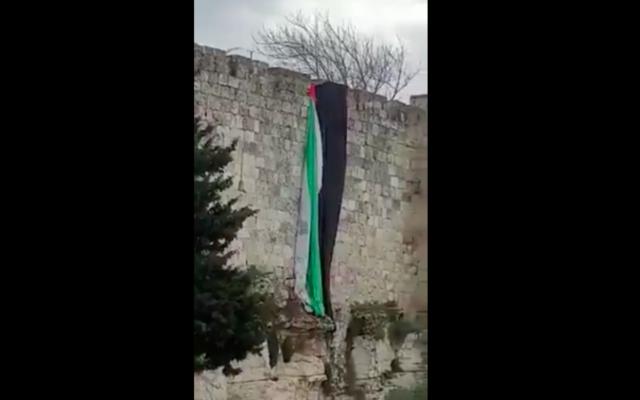 Capture d'écran d'une vidéo montrant le retrait d'un drapeau géant des murs de la Vieille Ville de Jérusalem. (Crédit : Twitter)