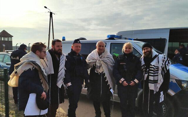 Les rabbins Shabbos Kestenbaum, Ezra Seligsohn, Avi Weiss et Jonathan Leener posent pour une photo avec la police après avoir protesté contre l'emplacement d'une église dans un ancien quartier général SS en face de l'ancien camp de la mort nazi de Birkenau, le 27 janvier 2020. (Yaakov Schwartz/ Times of Israel)