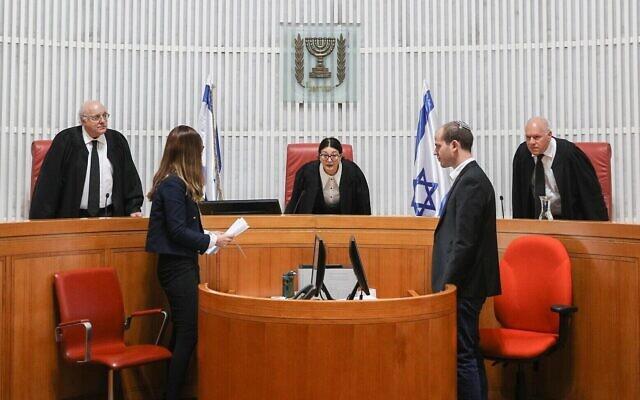 La présidente de la Cour suprême, Esther Hayut (au centre), arrive pour une audience préliminaire sur la question de savoir si un député faisant l'objet d'une inculpation pénale peut être appelé à former une coalition, le 31 décembre 2019. (Crédit : Yonatan Sindel/Flash90)