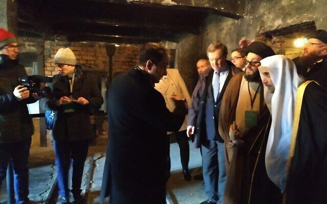 le secrétaire général de la Ligue islamique mondiale, Mohammed al-Issa, à droite, observe les équipements utilisés pour incinérer les Juifs à Auschwitz, le 23 janvier 2020. (Yaakov Schwartz/ Times of Israel)