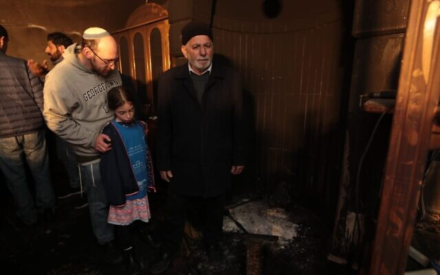 (De gauche à droite) Un père et sa fille se tiennent à côté de Muchtar Ismail Awad lors d'une visite de solidarité dans une mosquée de Sharafat qui a été incendiée lors d'un crime de haine présumé le 25 janvier 2020. (Tag Meir)