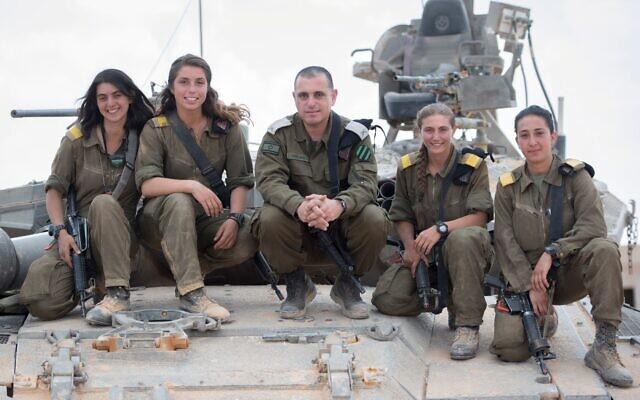 Le chef de forces blindés de l'armée israélienne, le général Guy Hasson, au centre, prend la pose sur un tank avec la première femme commandant de l'armée, qui a terminé sa formation , le 28 juin 2018. (Tsahal)