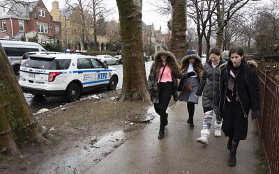 Des jeunes filles juives passent à côté d'une voiture de police garée dans le quartier de  Crown Heights le lundi 30 décembre  2019 dans le district de Brooklyn à New York. (AP Photo/Mark Lennihan)