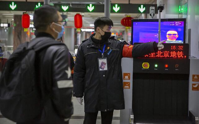 Un agent de sécurité dirige un homme vers une caméra thermique à une station de métro à Pékin, le mercredi 29 janvier 2020.  (AP Photo/Mark Schiefelbein)