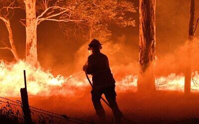 Un pompier australien arrose des arbres pour protéger des maisons avoisinantes des feux de forêts à proximité de la ville de Nowra dans l'état de South Wales, le 31 décembre 2019. Les incendies ont conduit à l'évacuation des zones populaires des touristes dans l'état. (Saeed Kahn/AFP)