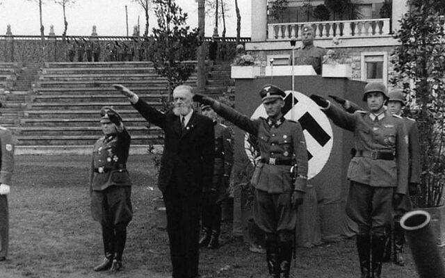 Leon Rupnik, portant un costume, fait le salut nazi avec des soldats allemands en Slovénie entre 1943 et 1945. (Archives de la République de Slovénie via JTA)