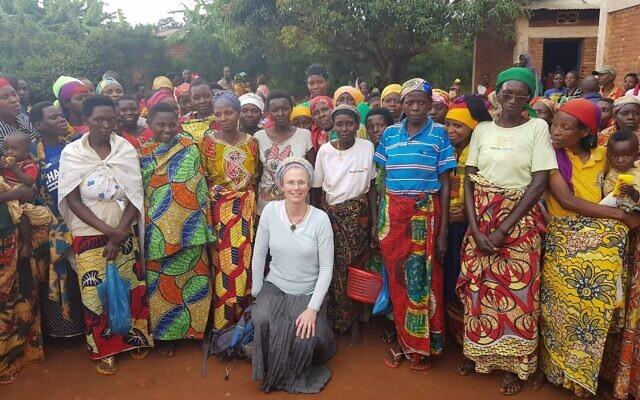 La coopérative de femmes du village de Mubuga qui devrait bénéficier des utilisations productives de l'énergie solaire dans le cadre d'un programme de développement social et économique. Hanna Klein (au centre), vice-présidente de la recherche et du développement des projets de Gigawatt Global, prévoit de faire passer l'électricité des moulins à farine du village du diesel à l'énergie solaire. (Autorisation)