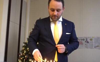 Le législateur Michael Freilich allume les bougies de Hanoukka au Parlement fédéral belge à Bruxelles, Belgique, le 19 décembre 2019. (Michael Freilich)