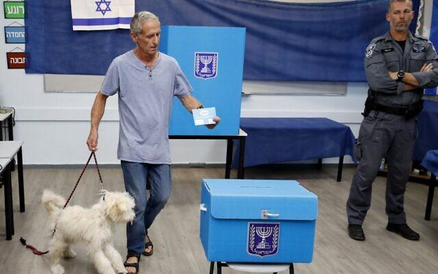 Un homme avec son chien vote dans un bureau de Rosh Haayin, le 17 septembre 2019. (Crédit : Jack GUEZ / AFP)