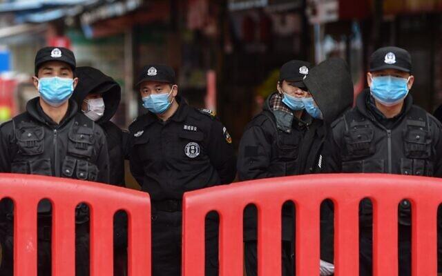 Des officiers de police et des gardes de sécurité montent la garde devant le Marché de fruits de mer d'Huanan où le coronavirus a été détecté à Wuhan, le 24 janvier 2020. (Photo par Hector RETAMAL / AFP)