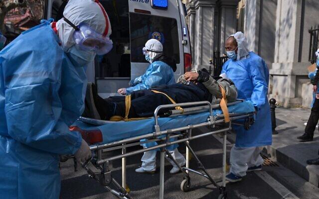 Des personnels médicaux en habit de protection transportent un patient depuis son appartement soupçonné d'être atteint par le virus à Wuhan, le 30 janvier 2020 (Crédit : Hector RETAMAL / AFP)