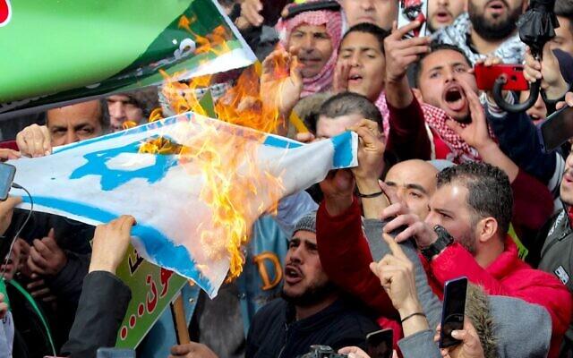 Des Jordaniens et des Palestiniens brûlent un drapeau israélien alors qu'ils participent à une manifestation à Amman, devant la mosquée al-Husseini au centre de la capitale, pour protester contre la proposition de paix présentée par les Etats-Unis pour le Moyen Orient, le 31 janvier 2020. (Crédit : Khalil MAZRAAWI / AFP)