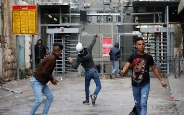 Des manifestants palestiniens lancent des pierres à un point de contrôle israélien lors d'affrontements avec les soldats israéliens dans le centre de la ville poudrière d'Hébron en Cisjordanie le 4 février 2020.  (Crédit : HAZEM BADER / AFP)