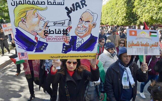 """Des manifestants tunisiens brandissent des pancartes contre la proposition de plan de paix du Moyen-Orient du président américain Donald Trump lors d'une manifestation le 5 février 2020 à Tunis. L'écriture arabe sur des pancartes se lit comme suit : """"Jérusalem est la capitale de la Palestine"""" (d) et """"A bas l'accord du siècle"""", #Boycott"""" à côté d'images de caricatures de Trump et du Premier ministre israélien Benjamin Netanyahu. (Crédit :  FETHI BELAID / AFP)"""