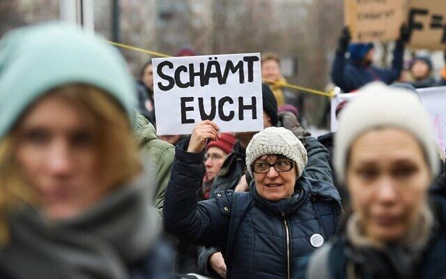 """Au lendemain de l'élection du Premier ministre de l'État de Thuringe, une femme tient une pancarte indiquant """"Honte à vous"""" lors d'une manifestation devant la chancellerie d'État à Erfurt, dans l'est de l'Allemagne, le 6 février 2020. (Crédit : Jens Schlueter / AFP)"""