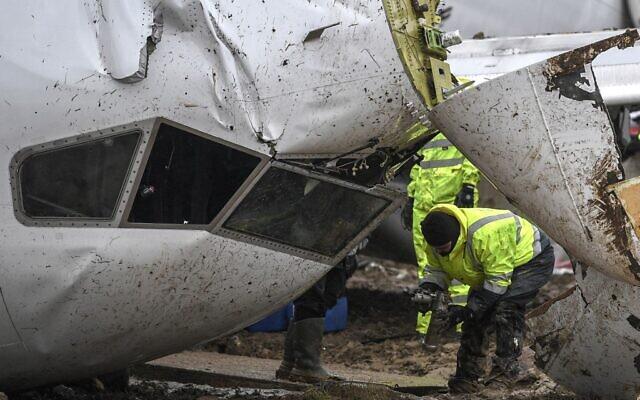 Un employé de la compagnie aérienne turque Pegasus inspecte l'épave du Boeing 737 qui est sorti de la piste et s'est brisé en trois parties lors de son atterrissage à l'aéroport Sabiha Gokcen, à Istanbul, le 6 février 2020. (Crédit : Ozan KOSE / AFP)