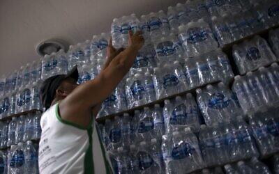 Un homme achète de l'eau en bouteille dans un magasin d'alcool du quartier de Lapa à Rio de Janeiro, le 15 janvier 2020. (Crédit : Mauro Pimentel / AFP)