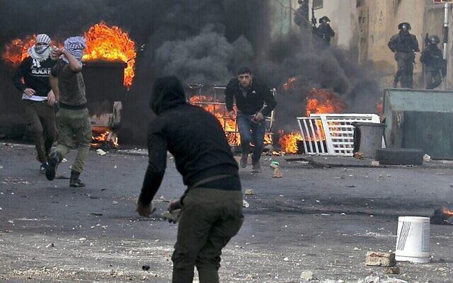 Les Palestiniens affrontent les forces de sécurité israéliennes pendant les funérailles du policier palestinien Tareq Badwa à Azzun, dans le nord de la Cisjordanie, le 7 février 2020 (Crédit : Jaafar Ashtiyeh/AFP)