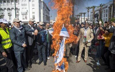 Des Marocains brûlent le drapeau israélien lors d'une manifestation contre le plan de paix américain pour le Moyen Orient dans la capitale Rabat, le 9 février 2020. (Crédit :  FADEL SENNA / AFP)