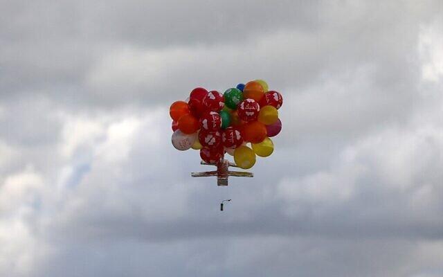 Des ballons transportent un dispositif incendiaire après avoir été lancés depuis le camp de réfugiés de Bureij, à Gaza, le long de la clôture entre Israël et Gaza, le 10 février 2020. (Crédit : MAHMUD HAMS / AFP)