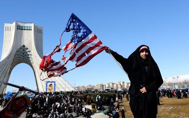 Une femme iranienne brandit un drapeau américain brûlé lors des commémorations marquant les 41 ans de la Révolution islamique sur la place Azadi, à Téhéran, le 11 février 2020. (Crédit : Atta KENARE / AFP)