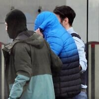 Des policiers transportant un suspect soupçonné d'être l'un des douze hommes arrêtés la veille dans le cadre d'une enquête nationale sur une cellule d'extrême droite, à son arrivée à la Cour suprême fédérale (Bundesgerichtshof) à Karlsruhe, dans le sud de l'Allemagne, le 15 février 2020. (Crédit : Uli Deck / DPA / AFP)