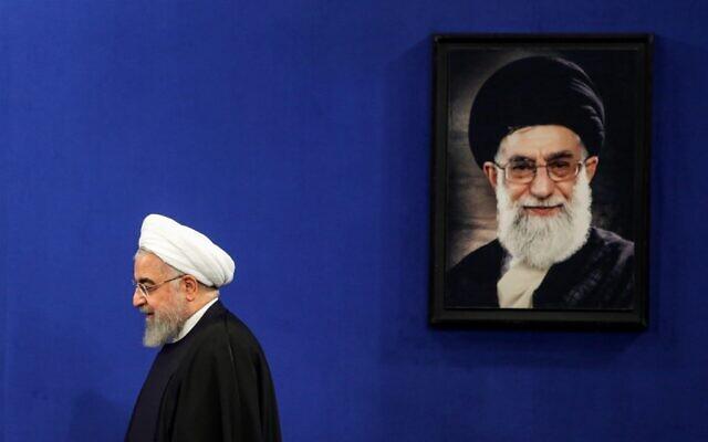 Le président iranien Hassan Rouhani passe devant un portrait du guide suprême, l'ayatollah Ali Khamenei, alors qu'il arrive pour une conférence de presse dans la capitale Téhéran, le 16 février 2020. (Photo ATTA KENARE / AFP)