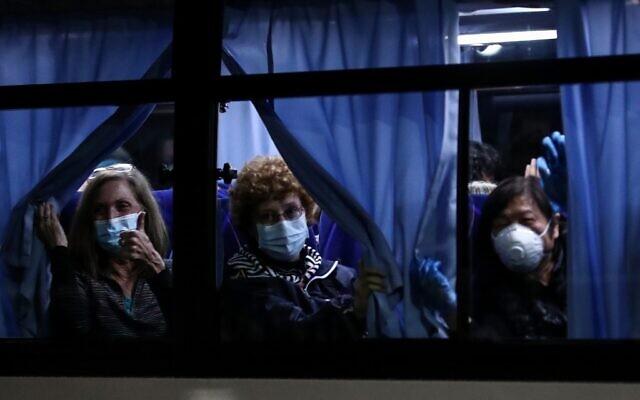 Des passagers américains saluent les journalistes en quittant le port de Yokohama,après avoir quitté le bateau de croisière Diamond Princess placé en quarantaine pour des craintes liées au nouveau coronavirus COVID-19 à Tokyo, le 17 février 2020 (Crédit :  Behrouz MEHRI / AFP)
