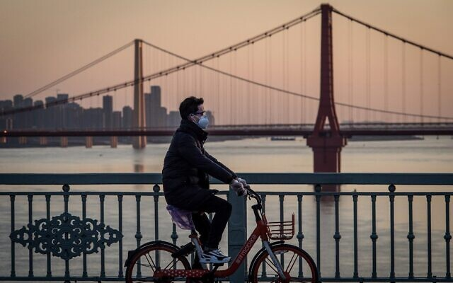 Un homme portant un masque de protection à vélo à Wuhan, dans la province centrale de Hubei, en Chine, le 17 février 2020. (Crédit :  STR / AFP )