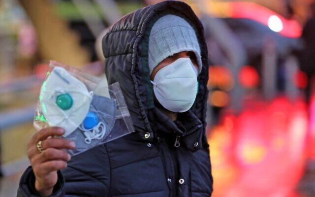 Un vendeur de rue iranien propose des masques de protection à Téhéran, le 20 décrier 2020. (Crédit : ATTA KENARE / AFP)