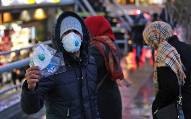 Un Iranien vend des masques de protection, à Téhéran le 20 février 2020. (Crédit : ATTA KENARE / AFP)