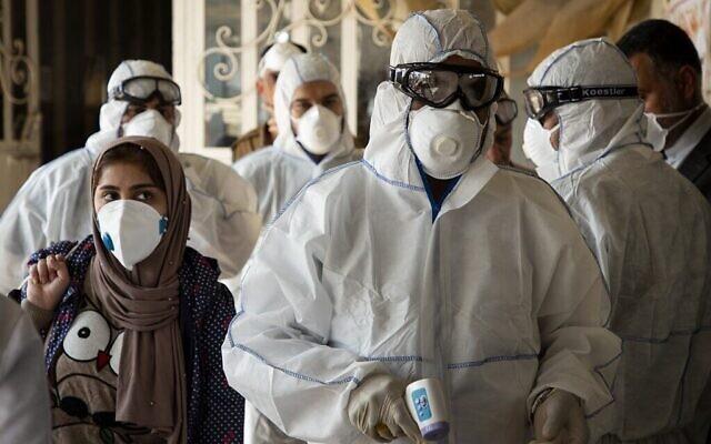Une équipe médicale contrôle les voyageurs au poste-frontière de Shalamjah, à environ 15 kilomètres de la ville irakienne de Basra à leur retour depuis l'Iran, le 21 février 2020 (Crédit : Hussein Faleh/AFP)
