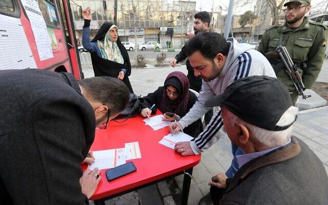 Un Iranien s'inscrit pour voter dans un bureau de vote mobile dans la capitale Téhéran le 21 février 2020. (Crédit : ATTA KENARE / AFP)