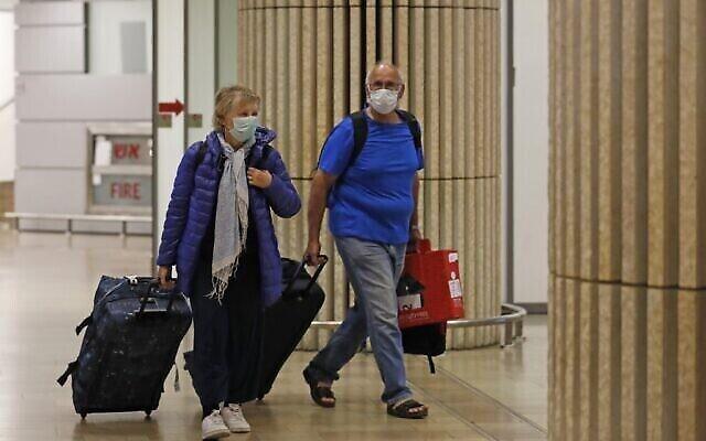 Des passagers portant des masques de protection traversent le hall d'arrivée de l'aéroport Ben Gurion le 22 février 2020. (Crédit : Ahmad Gharabli/AFP)