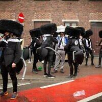 Des carnavaliers déguisés en Juifs ultra-orthodoxes avant le début du Carnaval d'Alost le 23 février 2020, Alost, Belgique. (Crédit : JAMES ARTHUR GEKIERE / AFP)