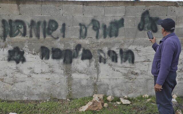 """Un homme prend en photo un slogan anti-arabe tagué en hébreu """"il y aura une guerre en Judée et Samarie"""" dans le village cisjordanien de Yasuf, à proximité de Naplouse, le 26 février 2020. (Photo par JAAFAR ASHTIYEH / AFP)"""