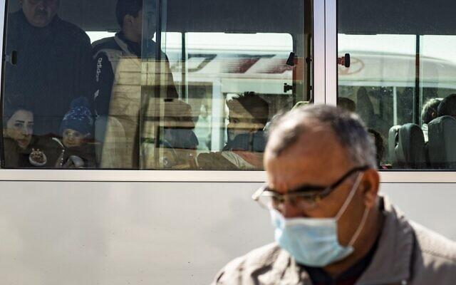 Un passager porte un masque par mesure de précaution contre le coronavirus à son arrivée en bus dans la zone kurde syrienne en provenance du Kurdistan irakien via le poste frontière de Semalka au nord-est de la Syrie le 26 février 2020. (Crédit : Delil SOULEIMAN / AFP)