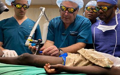Le Dr Josef Haik d'Israël montre au Dr Jerry Bernard, chirurgien haïtien, comment utiliser la machine laser, Milot, Haïti, janvier 2020. (Avec l'aimable autorisation du Burn Advocates Network)