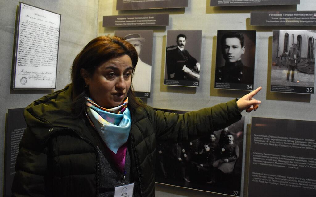 La guide touristique Aygün Agamirzayeva, parlant anglais, explique un panneau historique au complexe commémoratif du génocide de Quba. (Larry Luxner/ Times of Israel)