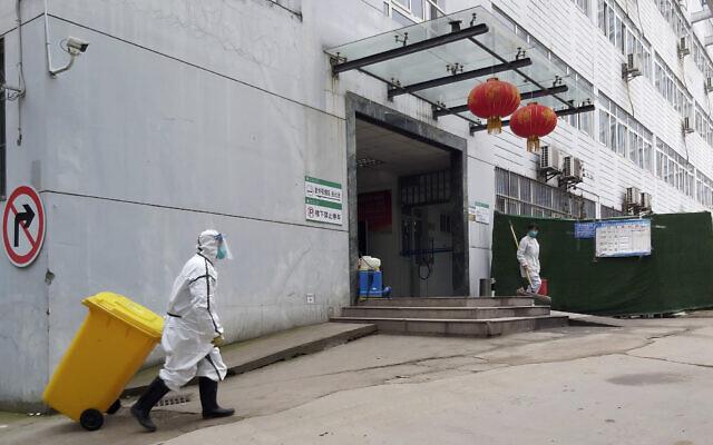 Sur cette photo du 23 janvier 2020, un membre du personnel portant une combinaison pour matières dangereuses transporte une poubelle dans un hôpital qui a signalé un décès par coronavirus à Yichang, dans la province de Hubei, en Chine centrale. (Chinatopix via AP)