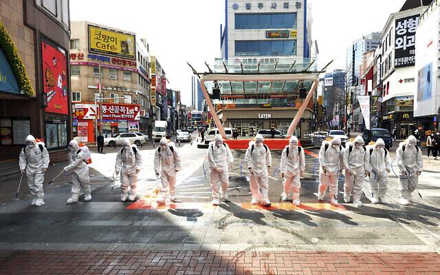 Des soldats de l'armée sud-coréenne portant des combinaisons de protection pulvérisent du désinfectant pour empêcher la propagation du virus COVID-19 dans une rue de Daegu, en Corée du Sud, le 27 février 2020 (Crédit : Lee Moo-ryul/Newsis via AP)