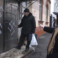 Illustration :le chef de la communauté juive Gennady Klebanov, à gauche, est sur le point d'entrer par la porte de la synagogue taguée de croix gammées, que le rabbin en chef de Vladivostok Isroel Silberstain, à droite, montre du doit, au port russe d'Extrême-Orient de Vladivostok, le 2 mars 2007. (Crédit : AP)
