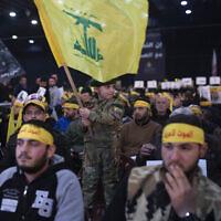 Un enfant en tenue militaire agite le drapeau du Hezbollah alors que des partisans du chef du groupe, Sayyed Hassan Nasrallah, attendent son discours télévisé dans une banlieue sud de Beyrouth, au Liban, le dimanche 5 janvier 2020, suite à l'attaque aérienne américaine en Irak qui a tué le général des Gardiens de la révolution iraniens Qassem Soleimani. (AP Photo/Maya Alleruzzo)