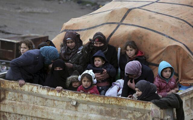 Des Syriens à l'arrière d'un camion fuient l'avancée des forces gouvernementales dans la province d'Idlib, en Syrie, vers la frontière turque, le 30 janvier 2020 (Crédit : Ghaith Alsayed/AP)