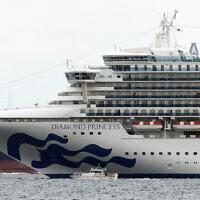 Un petit bateau navigue aux côtés du navire de croisière Diamond Princess, qui a posé l'ancre au port de Yokohama, près de Tokyo, au Japon, le 4 février 2020 (Crédit : Eugene Hoshiko/AP)