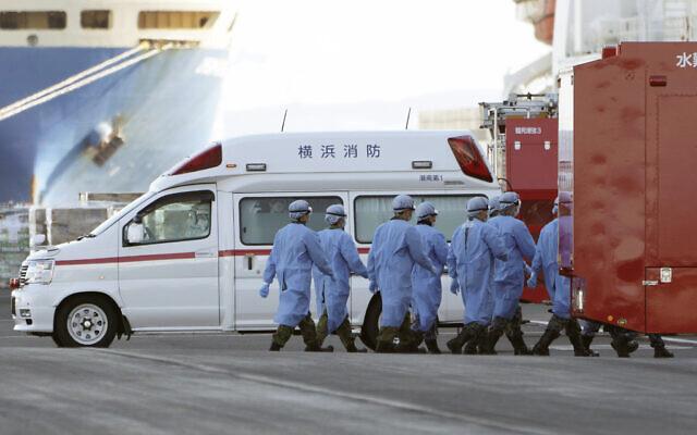 Les membres des forces d'auto-défense japonaises marchent vers le navire de croisière Diamond Princess mis en quarantaine sur le port de Yokohama au Japon, le 9 février 2020 (Crédit :  AP Photo/Eugene Hoshiko)