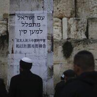 """Des Juifs prient au mur Occidental, dans la Vieille Ville de Jérusalem, lors d'une prière pour les malades du coronavirus apparu en Chine. L'affiche dit """"Le peuple d'Israël prie pour la Chine"""". Photo prise le 16 février 2020 (Crédit : Ariel Schalit/AP)"""