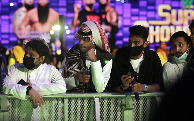 Des fans de lutte portent des masques de protection pendant qu'ils assistent à des matchs de lutte du WWE Super ShowDown à Riyad, en Arabie Saoudite, fin février 2020 (Crédit : AP Photo/Amr Nabil)