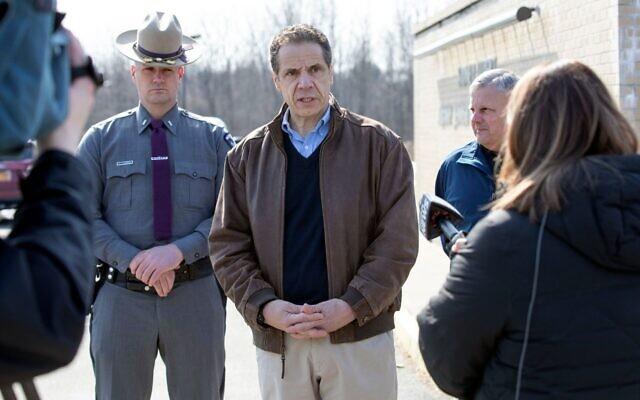 Le gouverneur de New York Andrew Cuomo, au centre, s'entretient avec des journalistes devant le centre communautaire juif Sidney Albert Albany après que le bâtiment a été évacué en raison d'une menace à la bombe envoyée par e-mail, le 24 février 2020. (Crédit : Mike Groll/Bureau du gouvernement Andrew Cuomo via JTA)